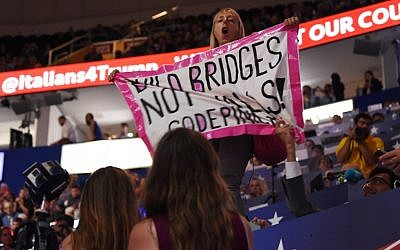 A Code Pink protestor shouts and holds a banner as Republican presidential candidate Donald Trump addresses the final night of the Republican National Convention at Quicken Loans Arena in Cleveland, Ohio, July 21, 2016. (AFP PHOTO/Robyn BECK)