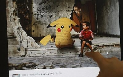 A journalist looks at a montage by a Syrian activist, using the international frenzy over the Pokemon Go game to draw new attention to the battle-scarred country, in Beirut on July 22, 2016. (Joseph Eid)