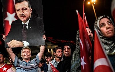A man holds up a photo of Turkey's President Recep Tayyip Erdogan during a Pro-Erdogan rally in Taksim square in Istanbul on July 22, 2016, following the failed military coup attempt of July 15. (AFP / OZAN KOSE)