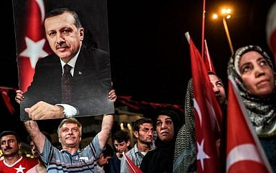 A man holds up a photo of Turkey's President Recep Tayyip Erdogan during a pro-Erdogan rally in Taksim Square in Istanbul on July 22, 2016, following the failed military coup attempt of July 15. (AFP/Ozan Kose)