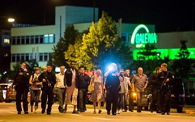 People are evacuated from the area around the shopping mall Olympia Einkaufzentrum OEZ in Munich on July 22, 2016 after a German-Iranian gunman  went on a shooting rampage in the busy shopping center, killing nine people. (AFP PHOTO/STRINGER)