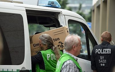 Police officers carry seized material after searching an appartment in the Dachauer Strasse in Munich on July 23, 2016, a day after a gunman went on a shooting rampage in the shopping mall Olympia Einkaufzentrum OEZ, killing nine people.  (AFP PHOTO/DPA/Tobias Hase)