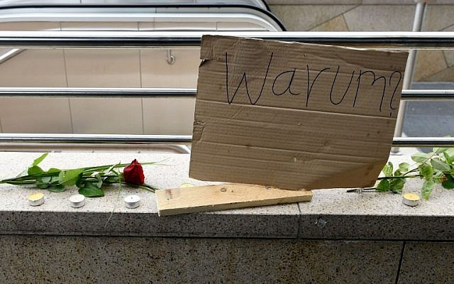 A poster reading 'Why?' rests next to flowers and candles in an impromptu memorial near a shopping mall in Munich on July 23, 2016, a day after a gunman went on a shooting rampage, killing nine people in a suspected terror attack. (AFP PHOTO/Christof Stache)
