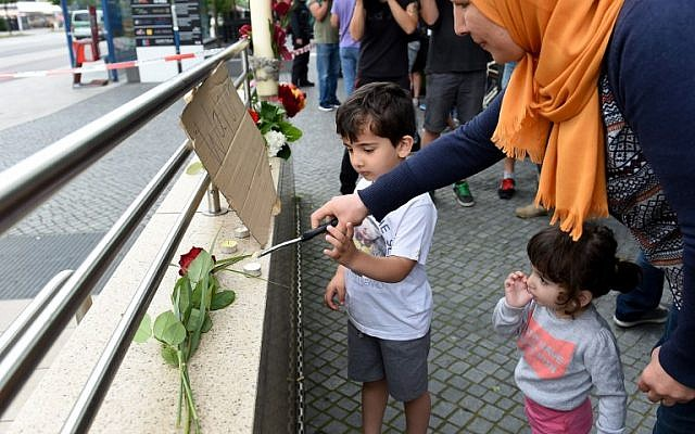 A veiled woman and her children lights candles to commemorate victims at the entrance of the subway station near the shopping mall Olympia Einkaufzentrum OEZ in Munich on July 23, 2016, a day after a gunman went on a shooting rampage, killing nine people in a suspected terror attack. (AFP PHOTO/Christof Stache)