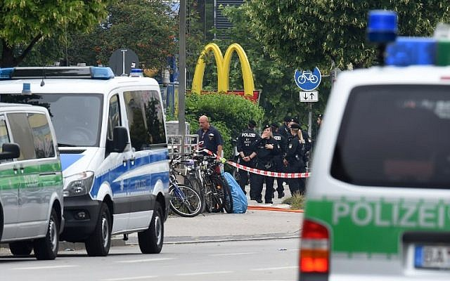 Police officers secure the area around a McDonald's restaurant near the shopping mall Olympia Einkaufzentrum OEZ in Munich on July 23, 2016, a day after a gunman went on a shooting rampage, killing nine people in a suspected terror attack. (AFP PHOTO/Christof Stache)