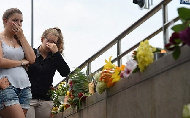 Two young women mourn at an underground station near the Olympia-Einkaufszentrum shopping center on July 23, 2016, one day after a shooting attack at the shopping center in Munich killed nine people. (AFP/ Christof Stache)