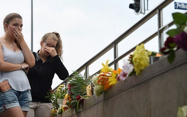 Two young women mourn at an underground station near the Olympia-Einkaufszentrum shopping centre on July 23, 2016, one day after the attack at the shopping centre in Munich, southern Germany. (AFP PHOTO / Christof Stache)