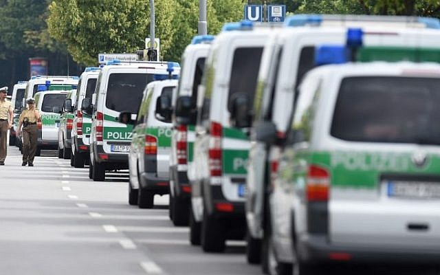 Police cars are parked near the Olympia-Einkaufszentrum shopping center on July 23, 2016, one day after a German-Iranian shooter killed nine people at the shopping center in Munich, southern Germany. (AFP/ Christof Stache)