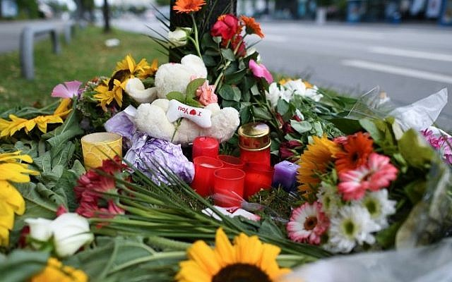Candles and flowers are placed on July 23, 2016 in Munich, southern Germany, near the scene of a shooting, one day after the attack at the shopping center in the Bavarian capital in which nine people were killed. (AFP/ dpa / Sven Hoppe)