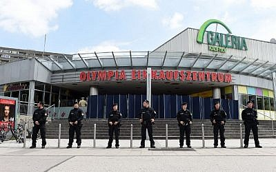 Policemen stand in front of the Olympia-Einkaufszentrum shopping center on July 23, 2016 in Munich, southern Germany, one day after a teenage German-Iranian gunman killed nine people and wounded 16. (AFP/ Christof Stache)