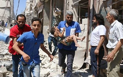 A Syrian civil defense volunteer carries a wounded child following a reported airstrike on the rebel-held neighborhood of Qatirji in the northern city of Aleppo on July 23, 2016. (AFP PHOTO/Thaer Mohammed)