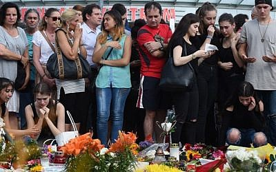 People mourn in front of candles and flowers on July 24, 2016 in front of the Olympia Einkaufszentrum shopping center in Munich, southern Germany, where an 18-year-old German-Iranian student run amok. (AFP / Christof Stache)