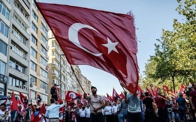 A demonstrator waves a Turkish flag near Istanbul's Taksim Square on July 24, 2016, during the first cross-party rally to condemn the coup attempt against President Recep Tayyip Erdogan. (AFP PHOTO / OZAN KOSE)