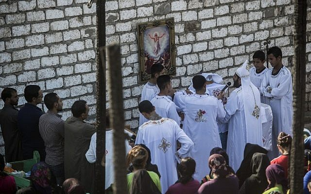 Egyptian Coptic Christians attend a mass in the rubble of a makeshift chapel that was torched during clashes a few earlier months earlier, in the Egyptian village of Ismailia, in the Minya governorate, July 24, 2016. (AFP/KHALED DESOUKI)