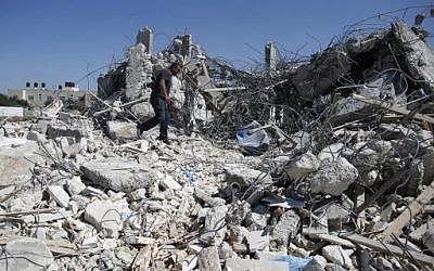 A Palestinian man walks atop the rubble of a house, demolished by Israeli army bulldozers, in the village of Qalandia, between the West Bank town of Ramallah and East Jerusalem, July 26, 2016. (AFP/Ahmad Gharabli)