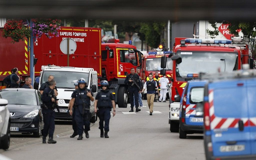 French police officers and firemen arrive at the scene of a hostage-taking at a church in Saint-Etienne-du-Rouvray, northern France, on July 26, 2016 that left the priest dead. (AFP PHOTO/CHARLY TRIBALLEAU)