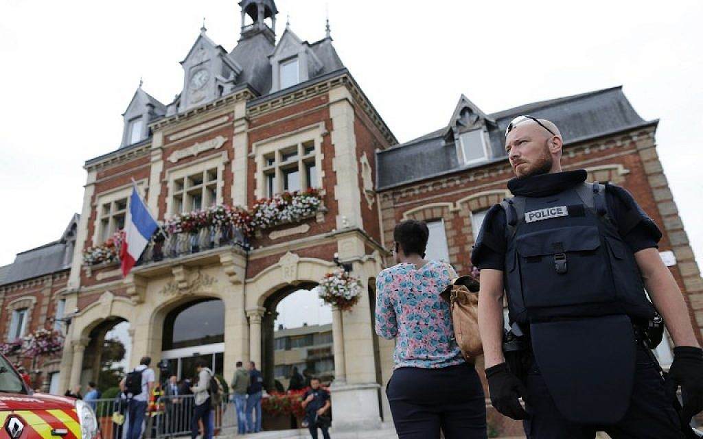 A French police officer stands guard by Saint-Etienne-du-Rouvray's city hall following a hostage-taking at a church in Saint-Etienne-du-Rouvray, northern France, on July 26, 2016 that left the priest dead.(AFP PHOTO / CHARLY TRIBALLEAU)