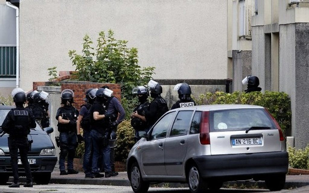 "French policemen stand in a street during a search in a house on July 26, 2016 in the Normandy village of Saint-Etienne du Rouvray after a priest was killed in the latest of a string of attacks against Western targets claimed by or blamed on the Islamic State jihadist group. French President said that two men who attacked a church and slit the throat of a priest had ""claimed to be from Daesh"", using the Arabic name for the Islamic State group. Police said they killed two hostage-takers in the attack in the Normandy town of Saint-Etienne-du-Rouvray, 125 kilometres (77 miles) north of Paris. / AFP PHOTO / MATTHIEU ALEXANDRE"