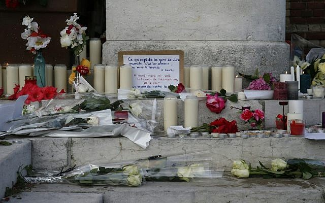 Flowers, candles and messages laid in front of the city hall in the Normandy town of Saint-Etienne-du-Rouvray in tribute to a priest killedby the Islamic State jihadist group, July 26, 2016. (AFP Photo/Mathieu Alexandre)