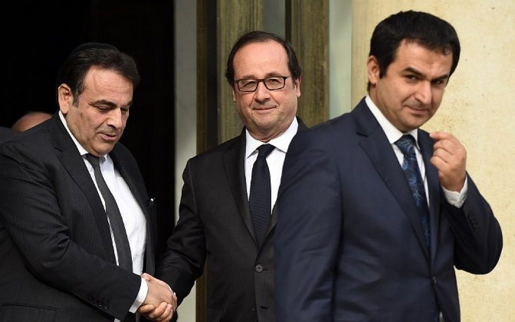 French President Francois Hollande (R) shakes hands with French Jewish central Consistory President Joel Mergui (L) outside the Elysee Palace in Paris, on July 27, 2016 as Ahmet Ogras, vice-president of the French Council of The Muslim Faith leaves after a meeting with French representatives of the different religion following yesterday attack at a church in Saint-Etienne-Du-Rouveray. (AFP PHOTO / BERTRAND GUAY