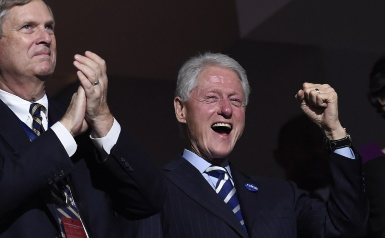 Former US president Bill Clinton, right, cheers as former New York City mayor Michael Bloomberg addresses the third evening session of the Democratic National Convention at the Wells Fargo Center in Philadelphia, Pennsylvania, July 27, 2016. (AFP/SAUL LOEB)