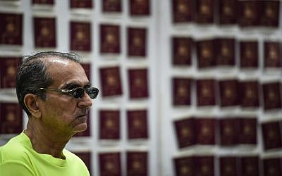 Abdullah Ghani Bhori, a Pakistani cohort of Iranian passport forger 'The Doctor' Hamid Reza Jafary (not pictured), looks on in front of fake Spanish passports at the Immigration Detention Center in Bangkok on July 22, 2016. (AFP PHOTO/LILLIAN SUWANRUMPHA)