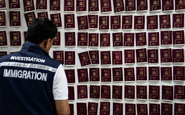 An immigration detective looks at forged Spanish passports at the Immigration Detention Center in Bangkok on July 22, 2016. (AFP PHOTO/LILLIAN SUWANRUMPHA)