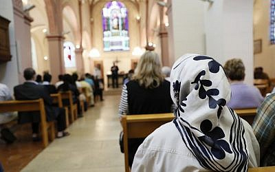 A Muslim woman sits as she attends a mass in tribute to priest Jacques Hamel at the Saint-Leu – Saint-Gilles Bagnolet's Church, near Paris, on July 31, 2016. (AFP Photo/Thomas Samson)