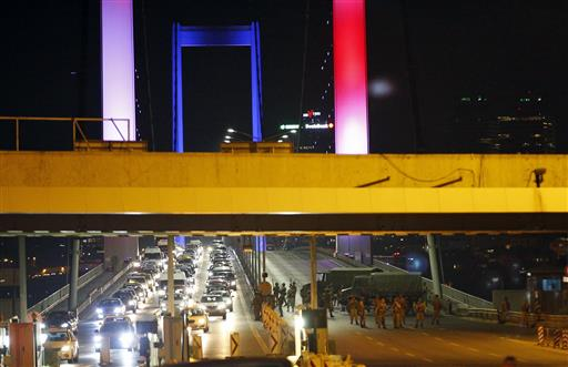Turkish soldiers block Istanbul's iconic Bosporus Bridge on Friday, July 15, 2016, lit in the colours of the French flag in solidarity with the victims of Thursday's attack in Nice, France. A group within Turkey's military has engaged in what appeared to be an attempted coup, the prime minister said, with military jets flying over the capital and reports of vehicles blocking two major bridges in Istanbul. (AP Photo/Emrah Gurel)