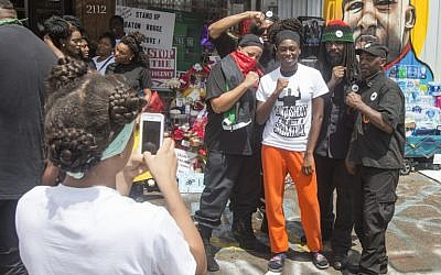 Cedrione Brown , center, has her photo taken with members of the New Black Panther Party in front of the Triple S Food Mart on July 9, 2016 in Baton Rouge, Louisiana. Alton Sterling was shot by a police officer in front of the Triple S Food Mart in Baton Rouge on July 5th, leading the Department of Justice to open a civil rights investigation. (Mark Wallheiser/Getty Images/AFP)