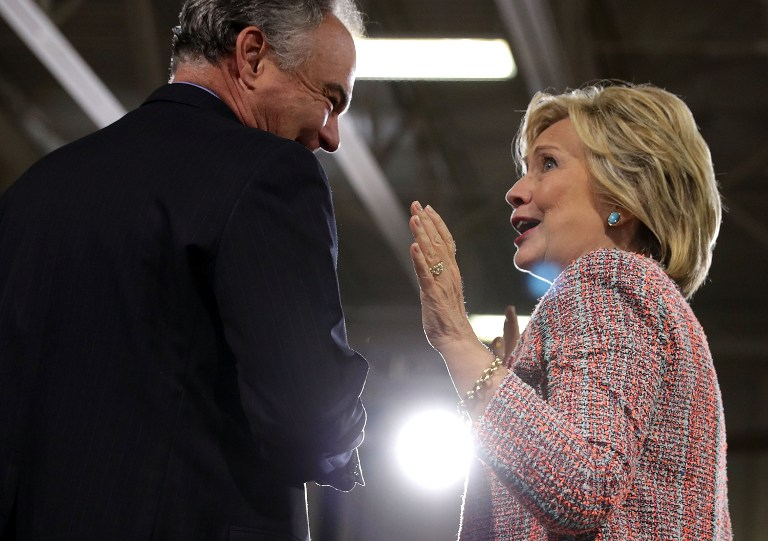 Democratic presidential candidate Hillary Clinton (R) and US Sen. Tim Kaine (D-VA) (L) share a moment during a campaign event at Ernst Community Cultural Center at Northern Virginia Community College July 14, 2016 in Annandale, Virginia. (Alex Wong/Getty Images/AFP)