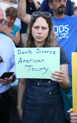 A protestor at a July 6, 2016 demonstration in front of the Jerusalem-based chief rabbis offices in support of the conversions of New York Rabbi Haskel Lookstein holds a sign reading, 'Don't Divorce American Jewry.' (Ezra Landau)