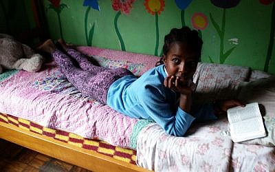 A girl reads the Bible in her bed at the Addis Ababa AHOPE Center for HIV-positive orphans, July 7, 2016 (Raphael Ahren/Times of Israel)