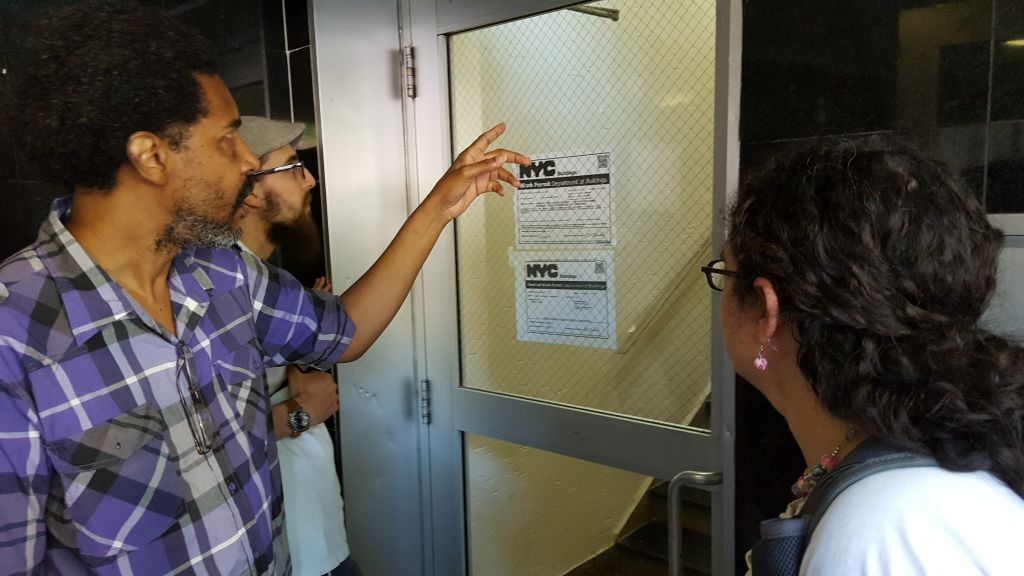 Bobby, an activist with Faith In New York, shows the fellows housing code violations that are being used to push poor tenants out of their homes in Flushing, NY. (Courtesy)