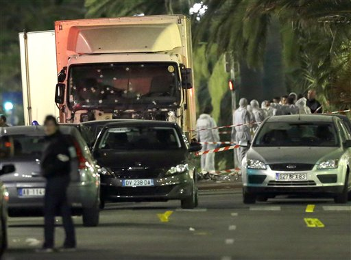 Forensic officers stand near a truck with its windscreen riddled with bullets, that plowed through a crowd of revelers who'd gathered to watch the fireworks in the French resort city of Nice, southern France, Friday, July 15, 2016. (AP Photo/Claude Paris)
