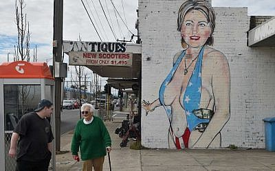People walk past a mural of US presidential nominee Hillary Clinton clad in a swimsuit, created by street artist Lushsux, in West Footscray, Melbourne on July 30, 2016 (Paul Crock/AFP)