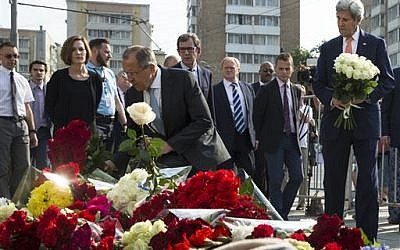 US Secretary of State John Kerry, right, and Russian Foreign Minister Sergey Lavrov, center, lay flowers at the French Embassy in Moscow, Russia on July 15, 2016, to pay condolences to victims of Thursday's terrorist attack in Nice, France. (AP Photo/Pavel Golovkin)