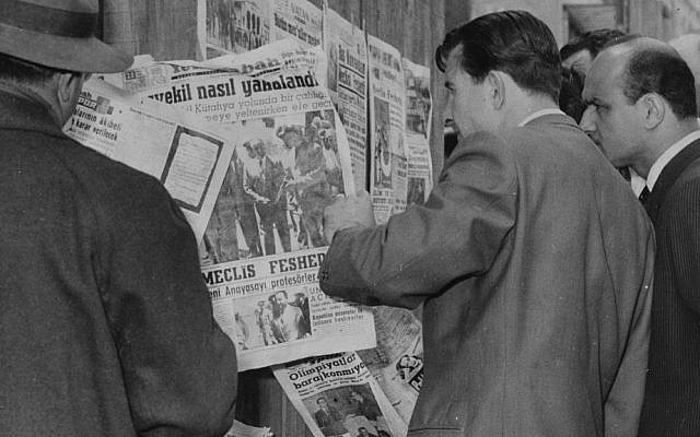 In this May 28, 1960 photo, citizens stand at a newsstand read of the capture of Prime Minister Adnan Menderes after a military coup, in Istanbul, Turkey. (AP Photo)