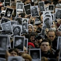People hold up pictures of those who died in the AMIA Jewish center bombing that killed 85 people as they commemorate the attack's 22nd anniversary in Buenos Aires, Argentina, July 18, 2016. (AP Photo/Natacha Pisarenko)