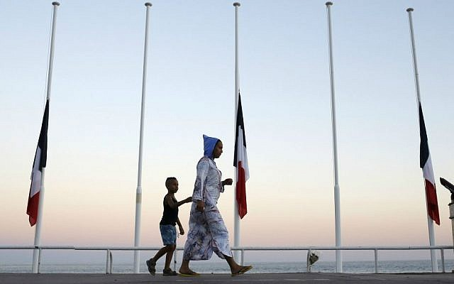 A woman and her child pass by French flags at half mast near the site of a deadly attack on the famed Boulevard des Anglais in Nice, southern France, Saturday, July 16, 2016. (AP Photo/Laurent Cipriani)
