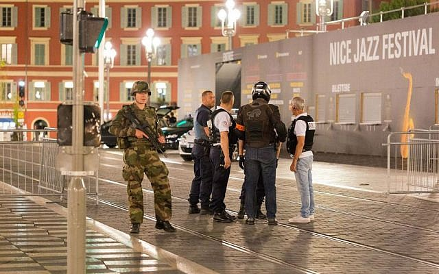 Police officers and a soldier stand by the sealed off area of a terror attack after a truck drove onto the sidewalk and plowed through a crowd of revelers who'd gathered to watch the fireworks in the French resort city of Nice, southern France, Friday, July 15, 2016. (AP Photo/Ciaran Fahey)