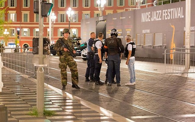 Police officers and a soldier stand alongside the sealed-off area of an attack after a truck drove onto the sidewalk and plowed through a crowd that was watching the Bastille Day fireworks in Nice, France, July 15, 2016. (AP/Ciaran Fahey)
