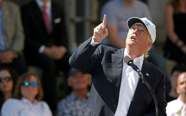 Republican presidential candidate Donald Trump points to an airplane passing overhead at a town hall-style campaign event at the former Osram Sylvania light bulb factory, Thursday, June 30, 2016, in Manchester, New Hampshire. (AP Photo/Robert F. Bukaty)
