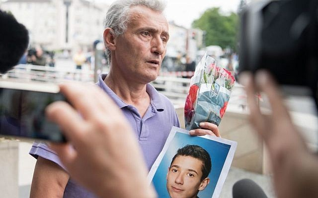 The father of a victim shows a picture of his son near the Olympia shopping center where a shooting took place leaving nine people dead the day before on Saturday, July 23, 2016 in Munich, Germany. (AP /Sebatian Widmann)