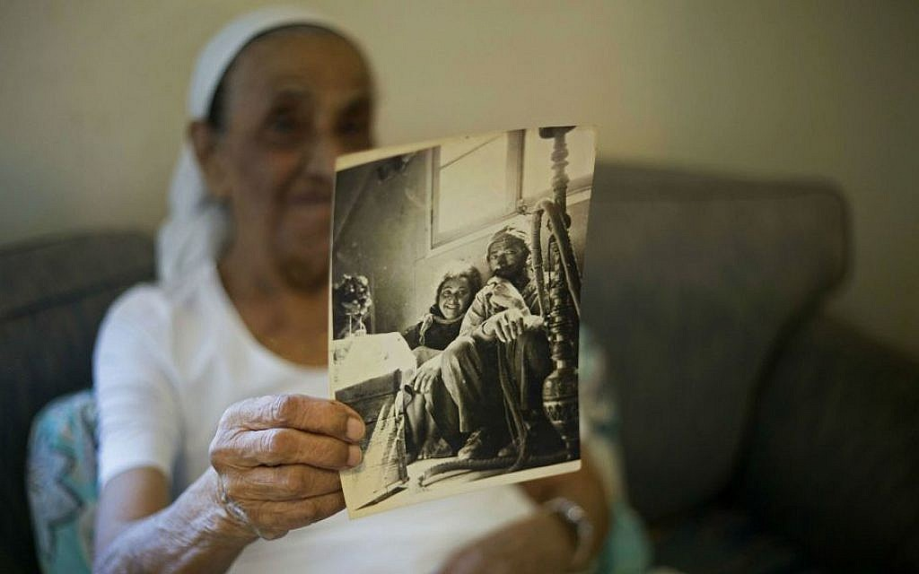 This Monday, July 11, 2016 photo shows Yemen-born Jewish Israeli Yona Josef holding a photograph dated back to the 1940's of her and her father back in Yemen, in her home in Ra'anana, Israel. (AP Photo/Ariel Schalit)