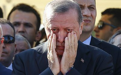 Turkish President Recep Tayyip Erdogan wipes his tears during the funeral of Mustafa Cambaz, Erol and Abdullah Olcak, killed Friday while protesting the attempted coup against Turkey's government, in Istanbul, Sunday, July 17, 2016. (AP Photo/Emrah Gurel)