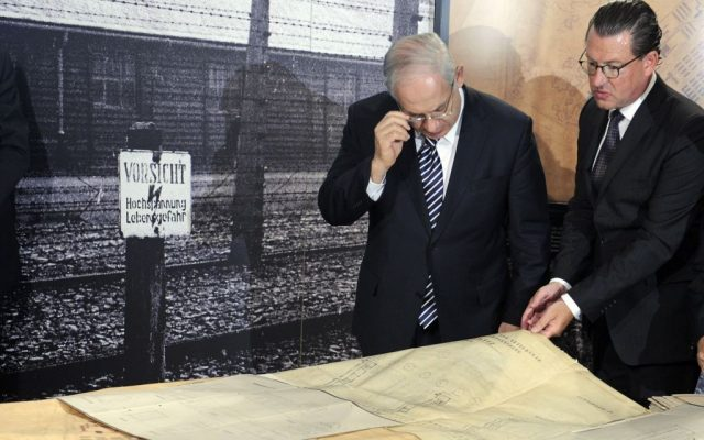 Prime Minister Benjamin Netanyahu, left, and 'Bild' newspaper chief editor, Kai Diekmann, right, look at original blueprints of the Nazi concentration camp in Auschwitz, Poland, in Berlin, Thursday, Aug. 27, 2009 (AP Photo/Rainer Jensen, Pool)