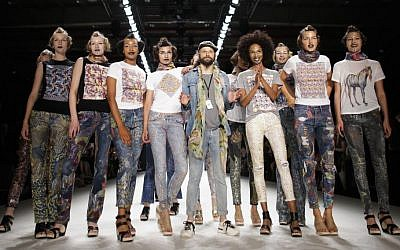 Designer Johny Dar, center, and the models receive the applause after the 'Jeans For Refugees project' fashion show Friday, July 1, 2016.  (AP Photo/Markus Schreiber)