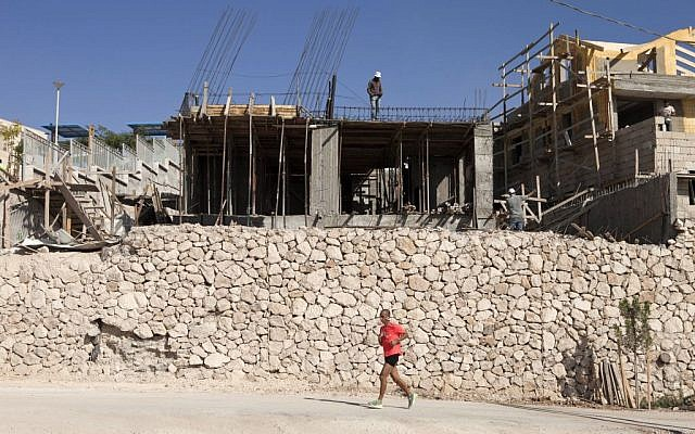 An Israeli jogs past Palestinians working at a construction site in the West Bank settlement of Ma'ale Adumim, near Jerusalem. (AP Photo/Dan Balilty)