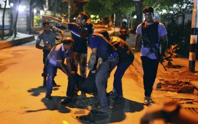People help an unidentified injured person after a group of gunmen attacked a restaurant popular with foreigners in a diplomatic zone of the Bangladeshi capital Dhaka, Bangladesh, Friday, July 1, 2016. (AP)